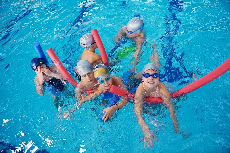 equipementier sportif natation enfants mettent bonnet de bain et lunettes de piscine jouer frites en mousse dans l'eau